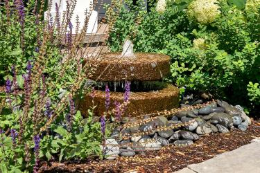 Round stacked stone water fountain in a front yard garden.