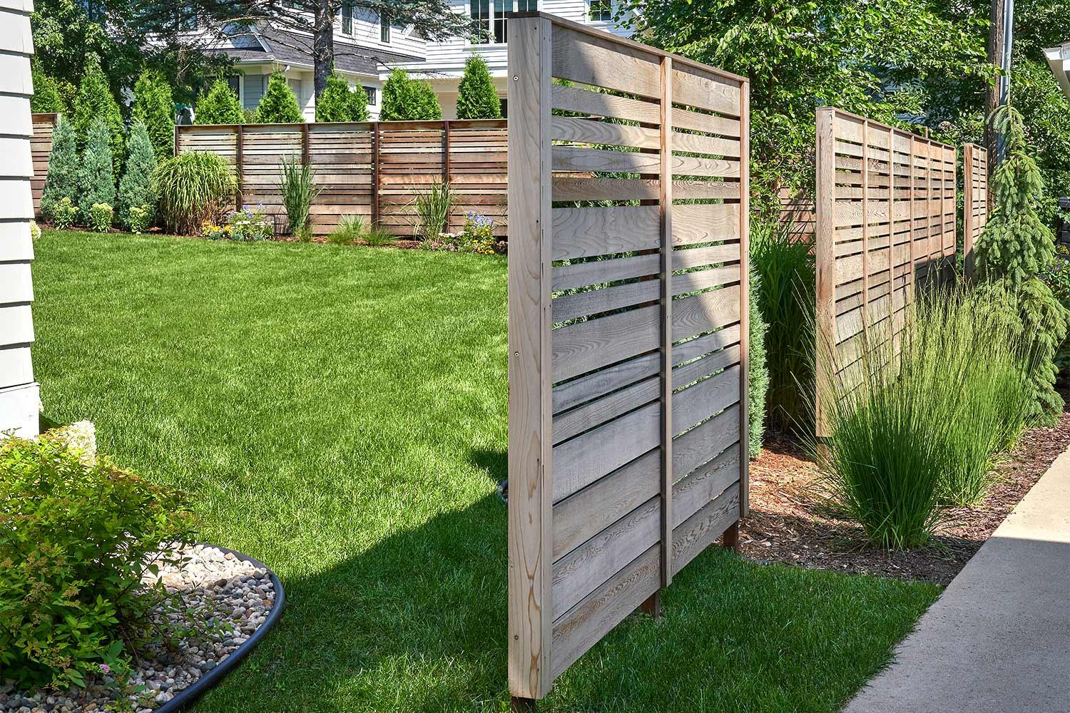 Horizontal slat fencing around the backyard and side perimeter of this Edina, MN landscape.