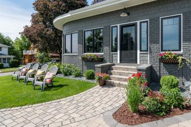 Permeable paver walkway leads to front door and steps past new lawn and four lawn chairs.