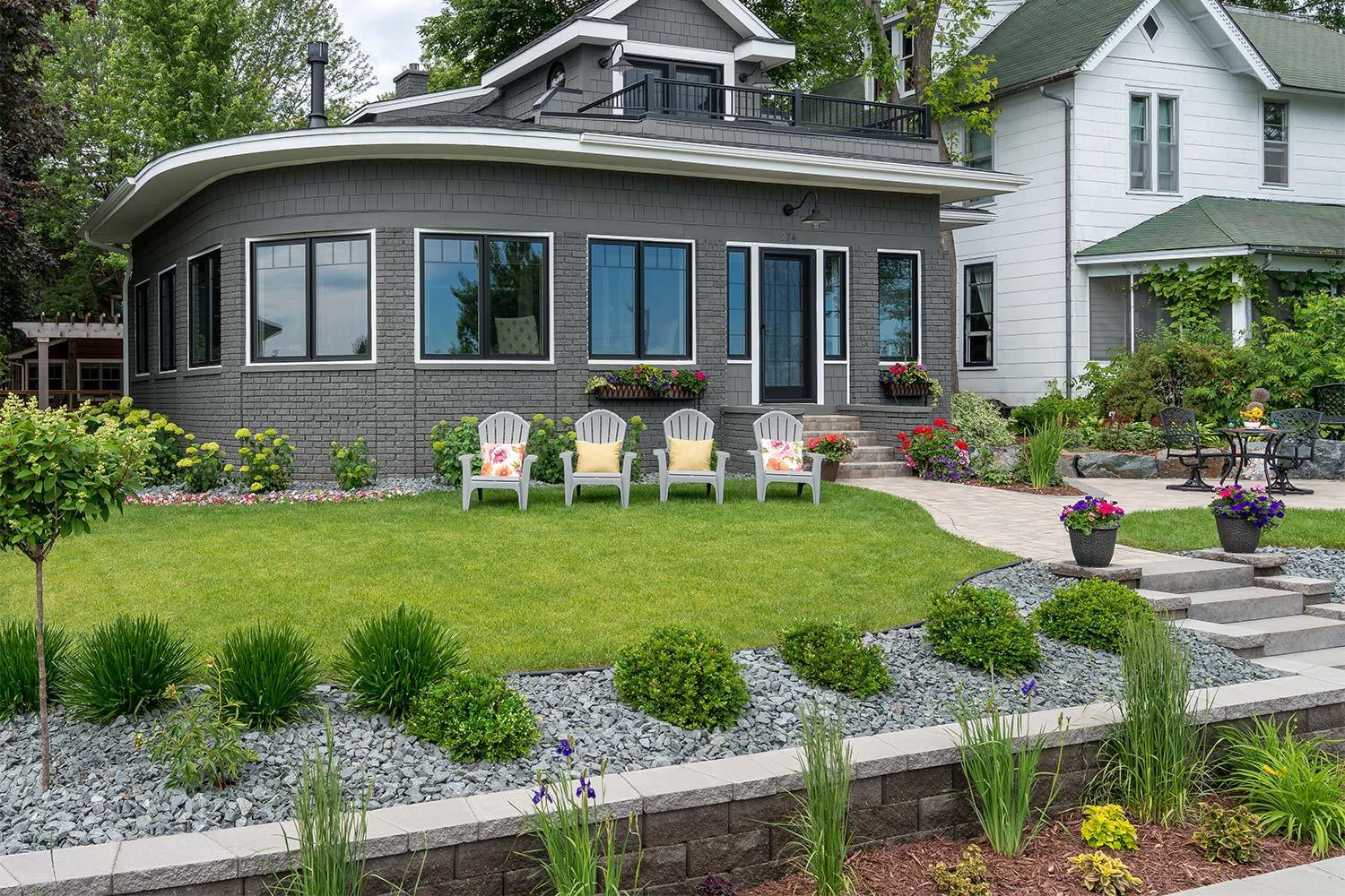 Lake Minnetonka front yard landscape design with formal garden, retaining wall, small patio and lawn with four chairs.