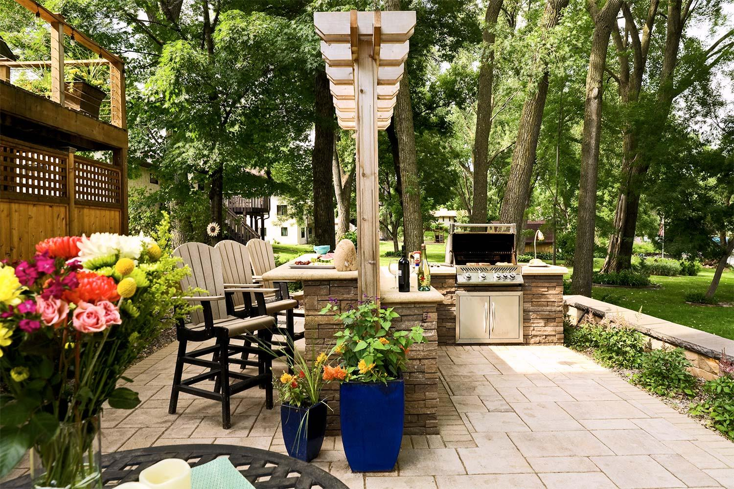 Backyard outdoor kitchen with an arbor, bar seating, and built-in gas grill.