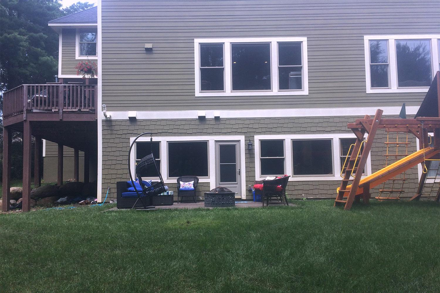 Typical suburban backyard with a lawn, small patio with furniture, and a child's jungle gym.