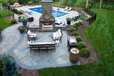 Bluestone patio with statement fireplace and unique bar set.