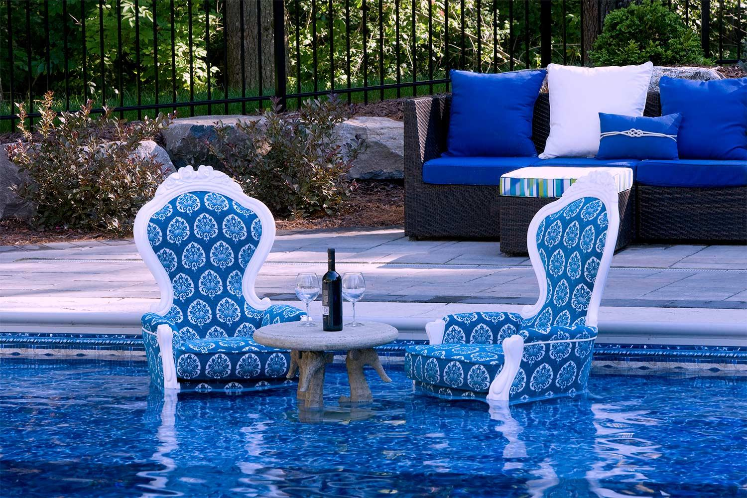Two blue chairs with a floral leaf pattern place directly into the swimming pool.