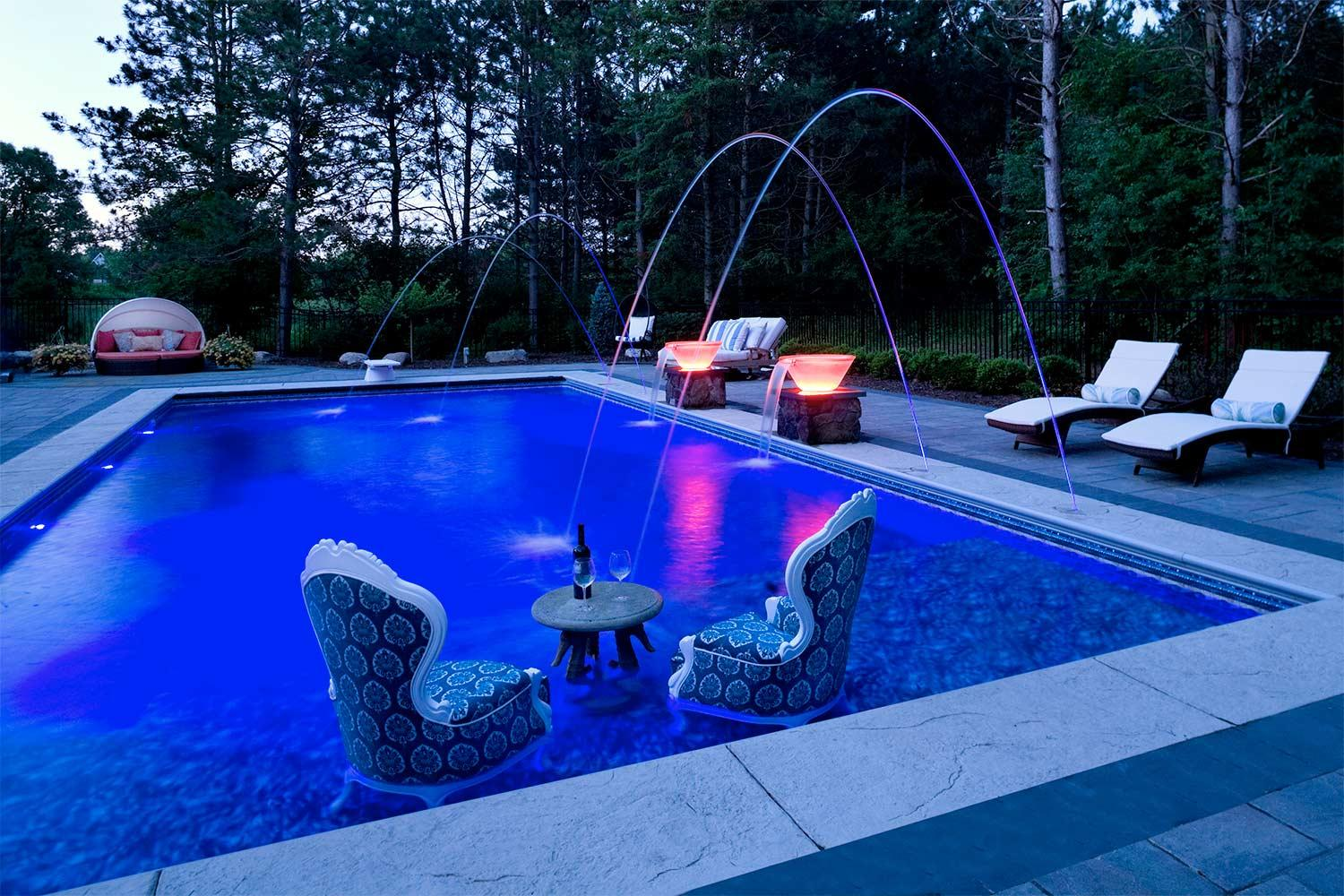 Two chairs in the swimming pool with illuminated water feature bowls and laminar jets ino the surface of the pool.