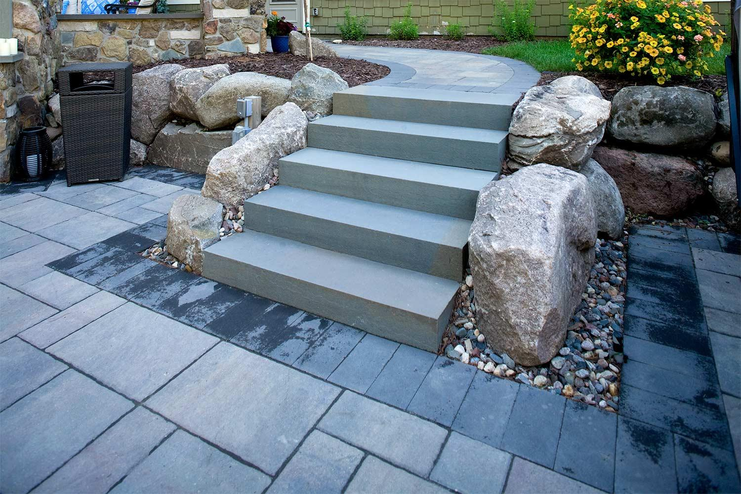 Outdoor stone stair case, boulder retaining wall, and paver patio.