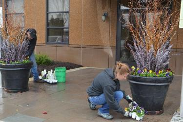 Man and woman working outside planting flower in large flower pots.