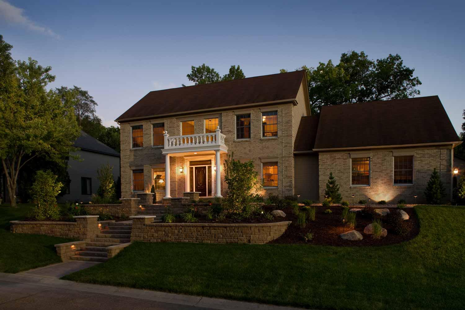 Night lighting highlights landscape and architectural elements of this formal front yard landscape design.