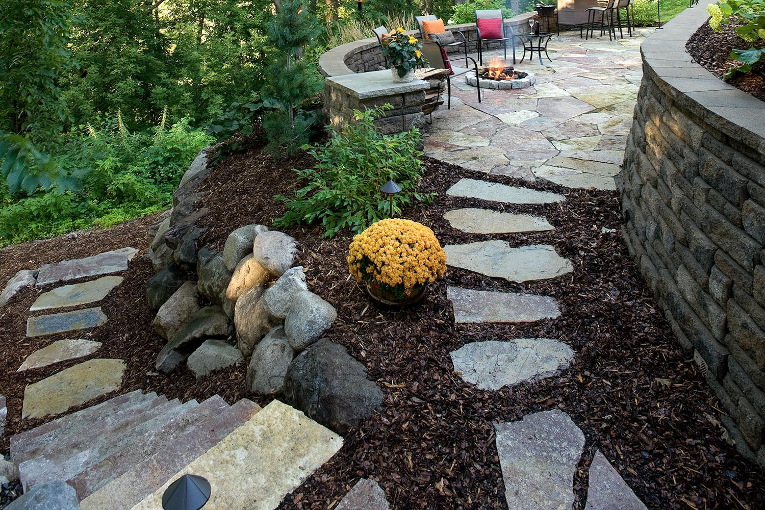 Modular retaining block wall creates a level space for an award-winning patio.