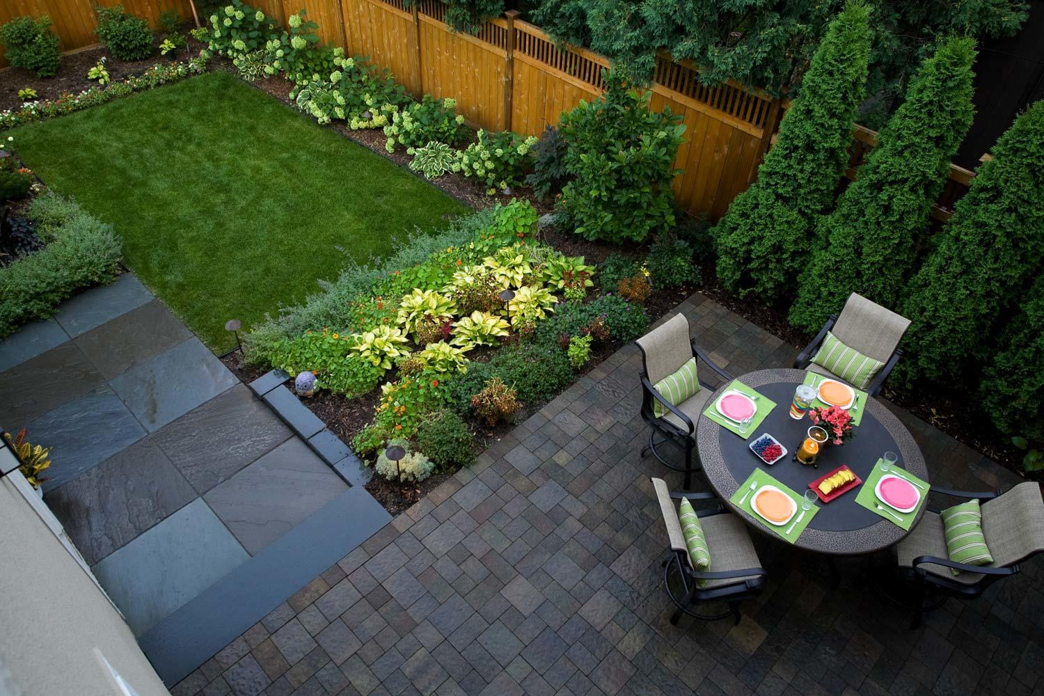 Small modern urban backyard with neatly divided walkways plantings and patios in Minneapolis Metro Area