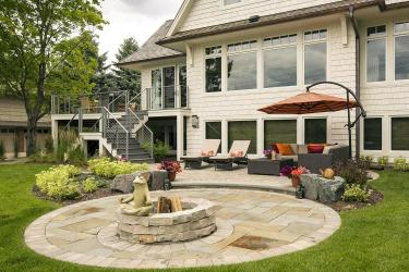 Circular backyard paver patios with a fire circle and meditating frog