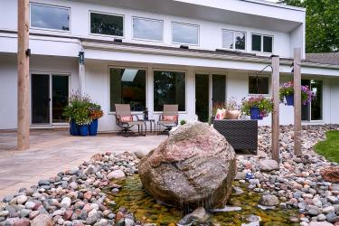 Statement water feature created from a boulder, placed in a river of stone bordering the living patio.
