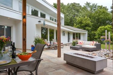 Expansive modern walk-out patio with dining area, fire table, and seating patio.