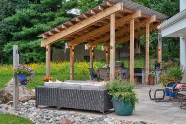 Outdoor kitchen under a modernist shade structure. Native yellow wildflowers in the background define the border between properties.