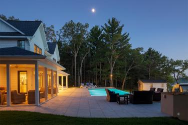 The moon shines bright in the sky over a pine forest and luxury lake house backyard with a swimming pool and porcelain tile patio.