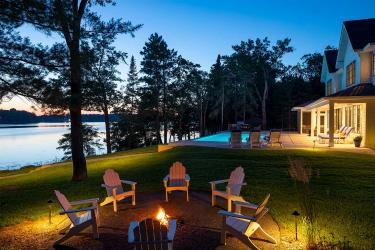 Northern Minnesota lakeshore landscape at dusk. A fire surrounded by a circle of white Adirondack chairs in the foreground, with the illuminated swimming pool and pool deck in the background.