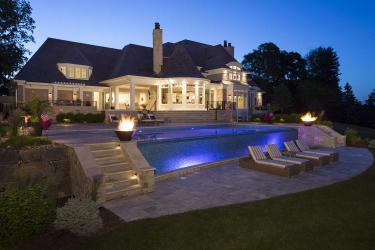 backyard swimming pool landscaping with fire features and night lighting