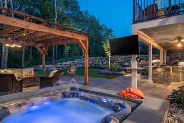 north woods style backyard hot tub with laminar jets and lighting