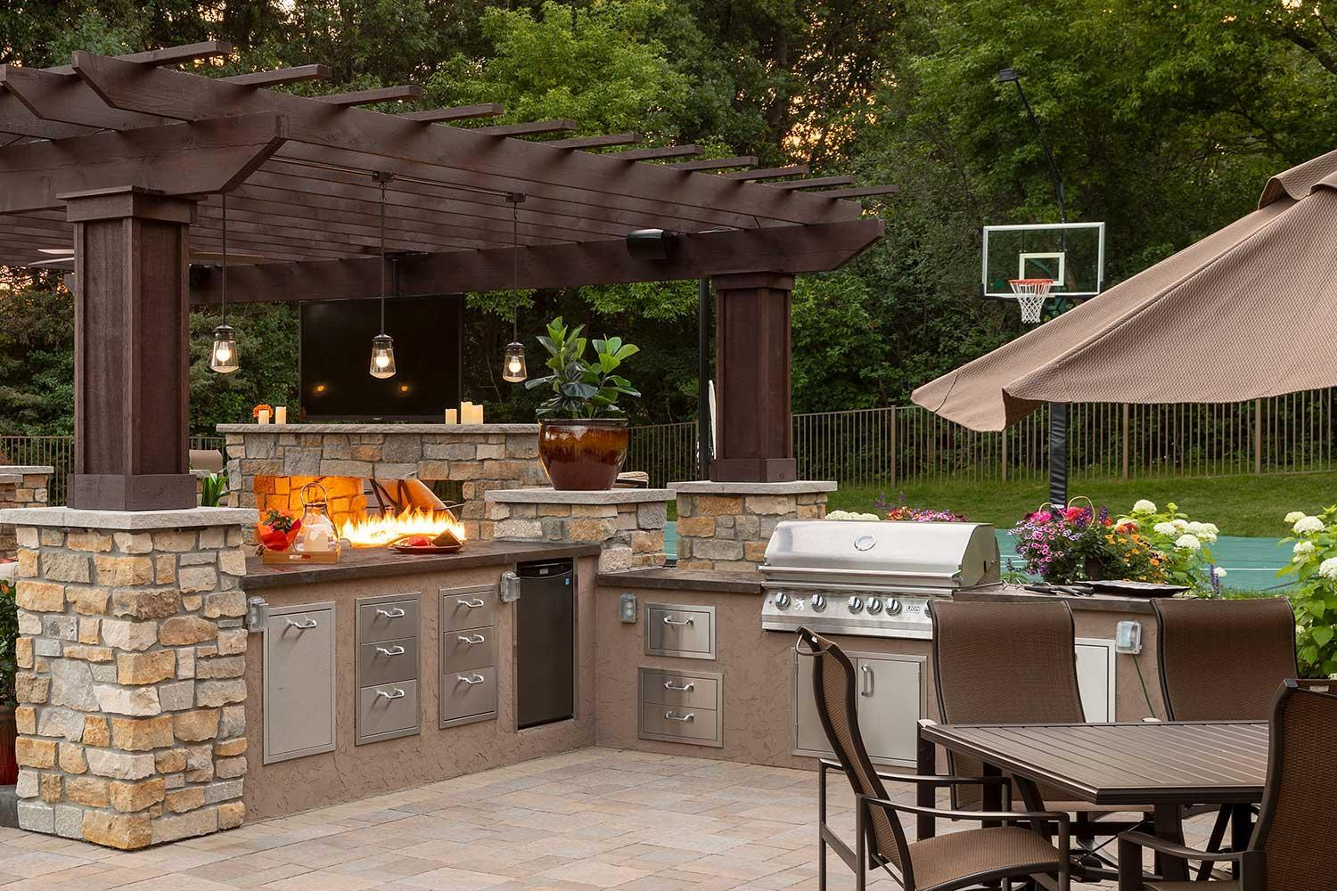 Outdoor kitchen and dining patio in a resort style backyard.