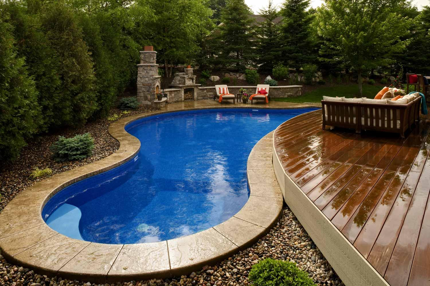 Curved backyard swimming pool fits around a deck and fire patio