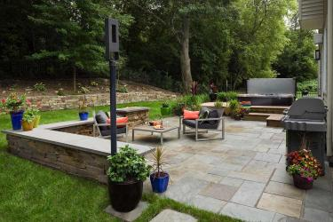 modern stone backyard patio with a stacked stone seat wall