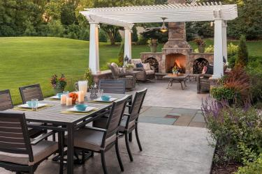 Outdoor backyard living and dining room patios with bluestone pathway.