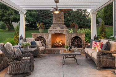 Living room patio with an oversized fireplace, ceiling fan, and pergola.
