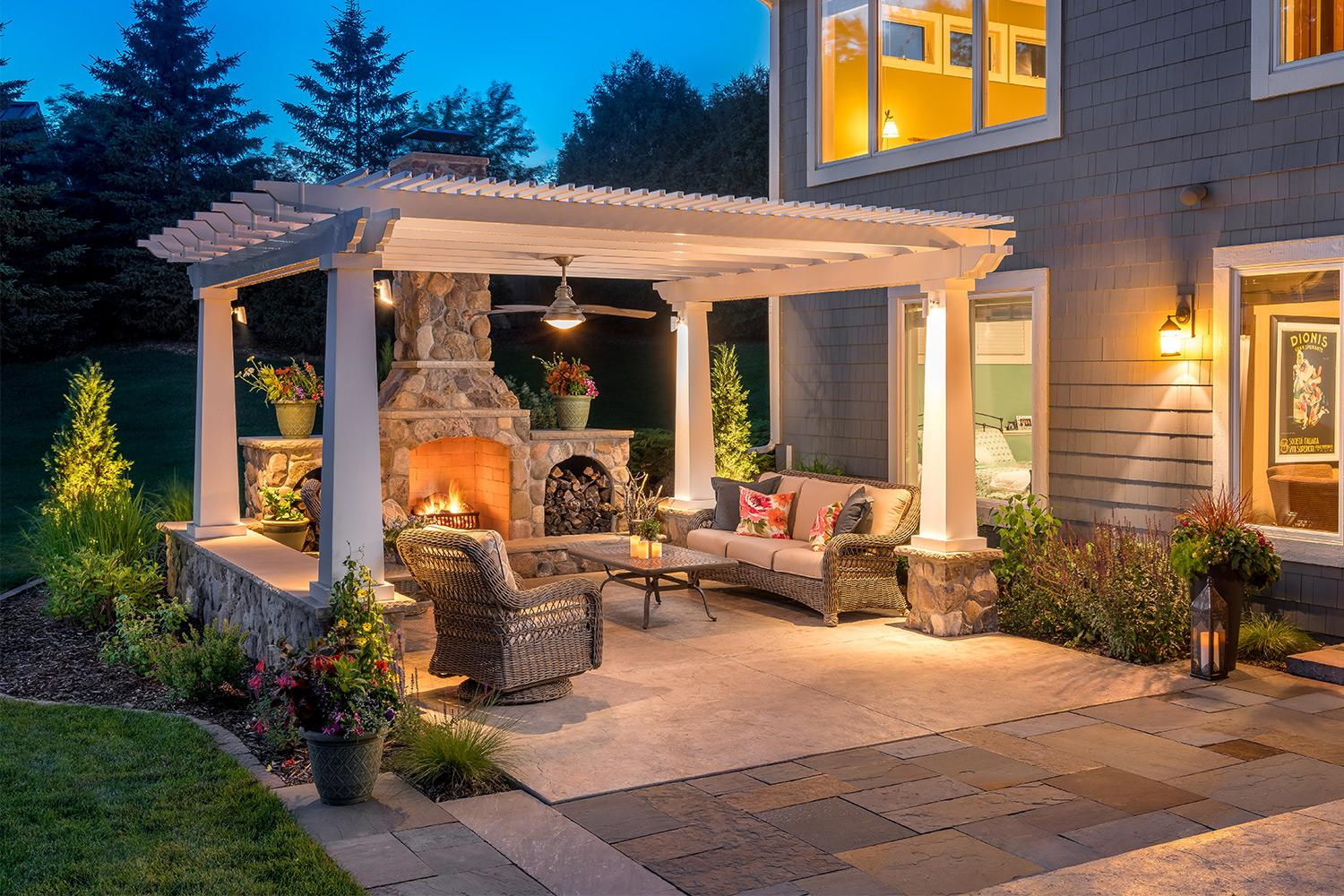 Outdoor living room patio with stone-faced fireplace underneath a white pergola at dusk