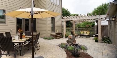 Backyard dining patio sheltered under an umbrella and a sitting patio underneath a pergola.