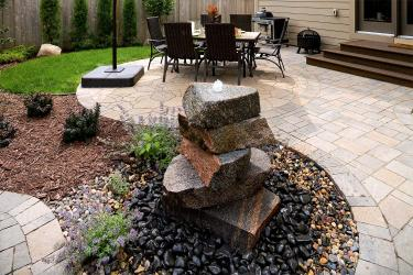 Stacked stone ornamental water fountain with dining patio and dog grass in the background.