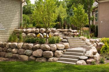 Boulder retaining wall with gardens and staircase