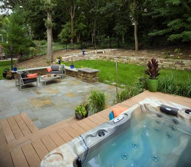Hot tub deck and bluestone patio, stacked stone retaining wall, and modern outdoor fireplace
