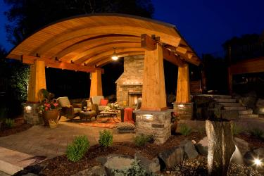 arched wooden outdoor structure sheltering patio furniture and fireplace at night