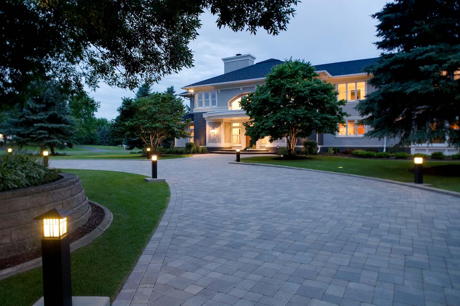 Elegant curving paver driveway flanked by tower lights