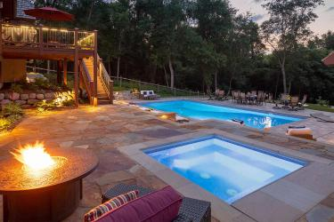 Fire table, hot tub, and swimming pool at dusk.