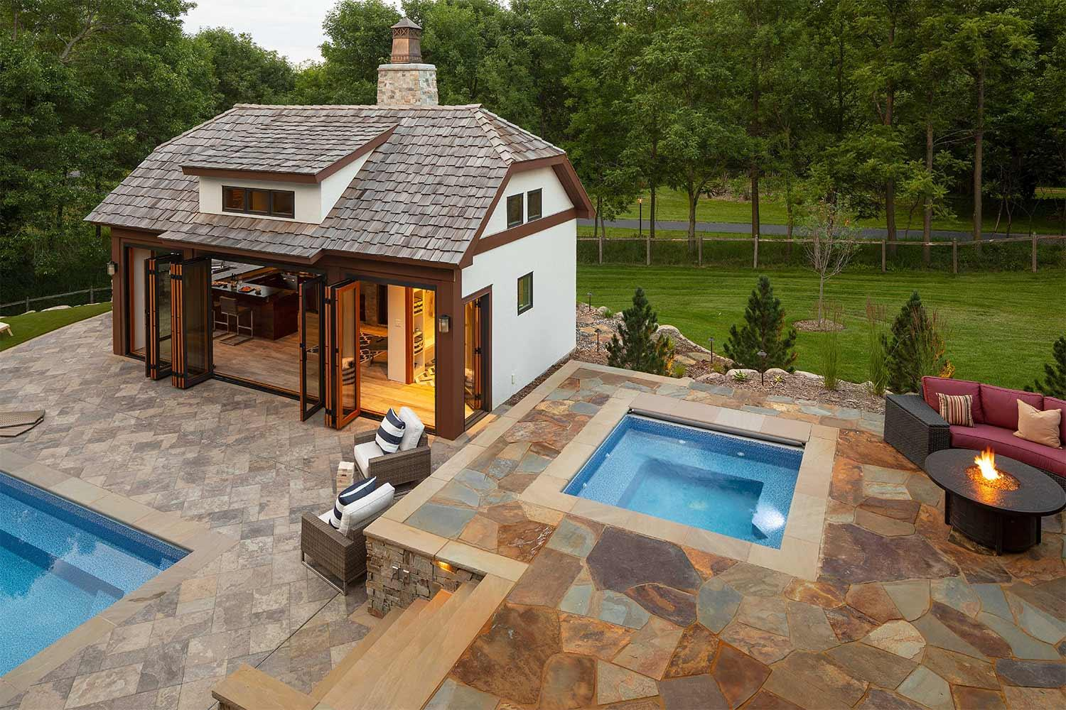 Pool house, hot tub, and natural stone patio and pool deck.