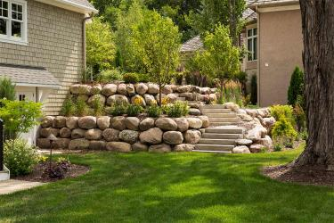 Bright green lawn in the shade. Boulder retaining wall and ornamental trees.