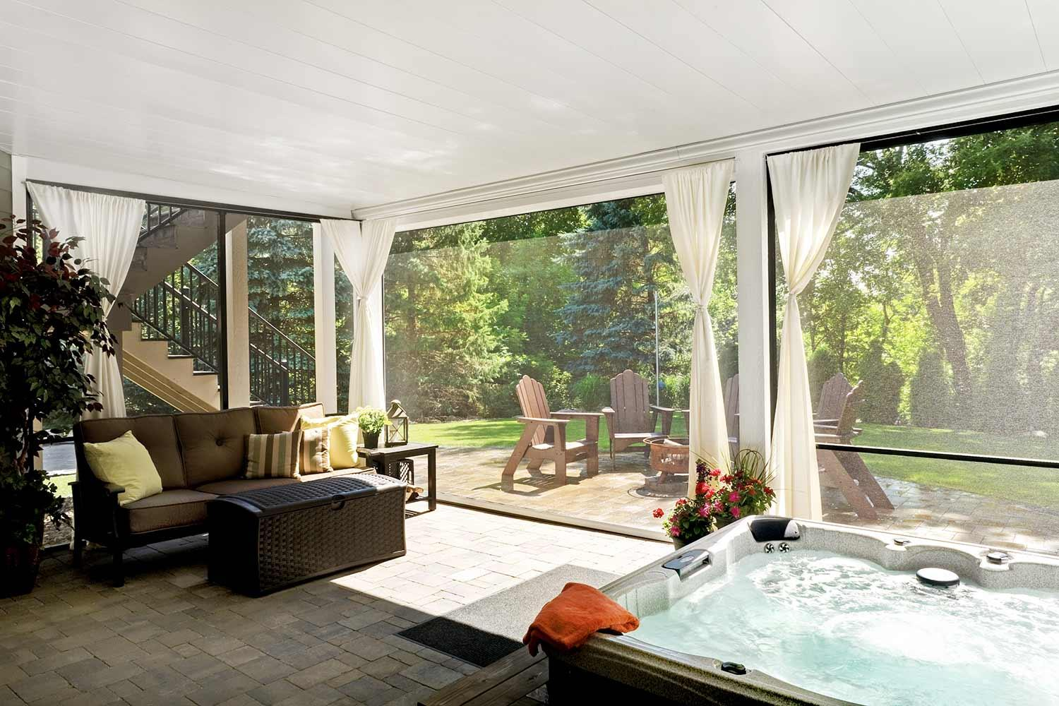 outdoor living room with hot tub and curtains