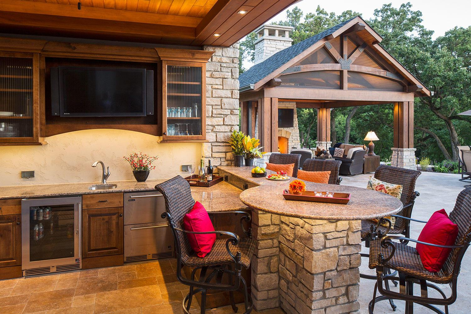 Outdoor Bar with TV, Beverage Cooler, and Sink. Pool house outdoor living room with fireplace and television