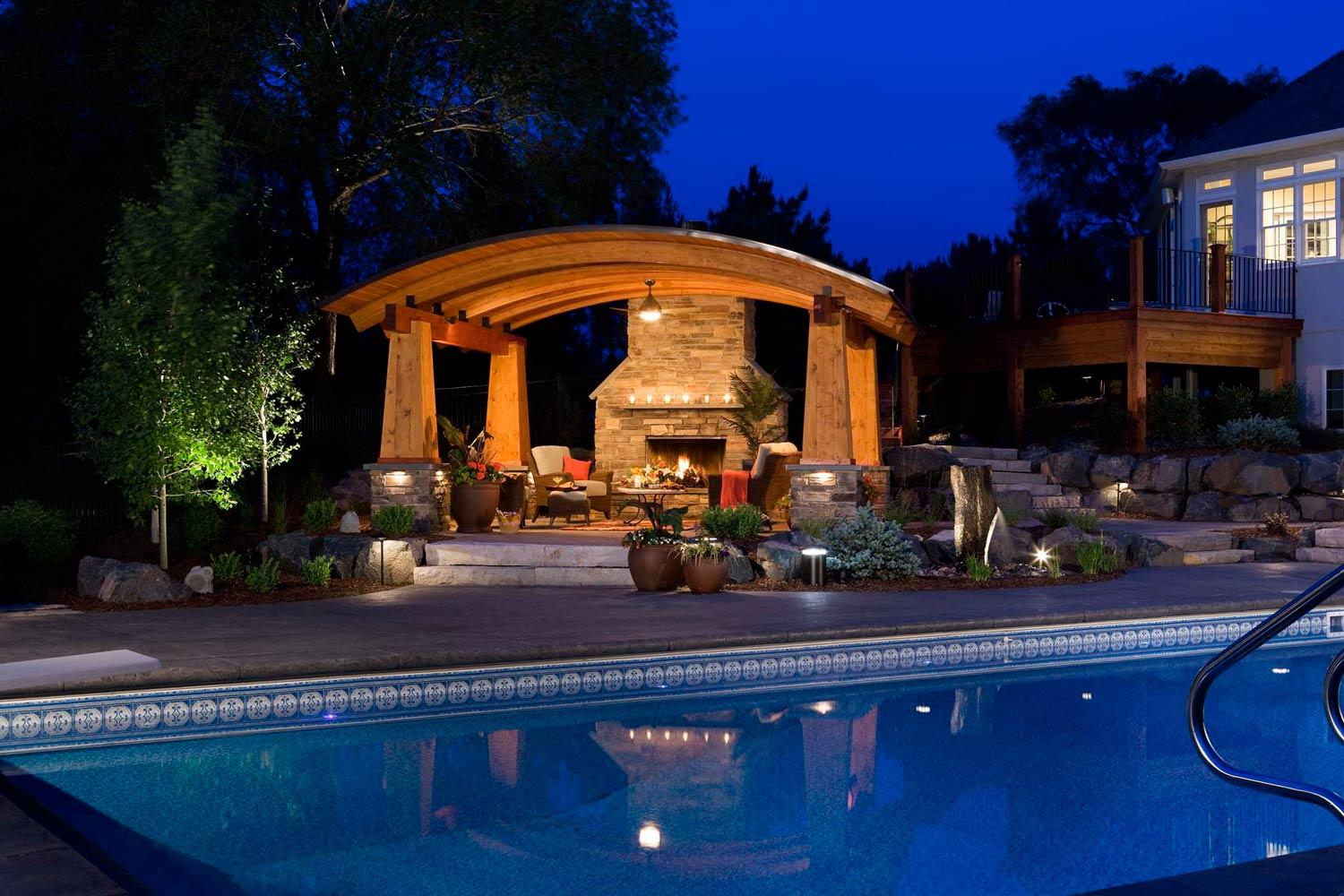 Outdoor living room, swimming pool, and elevated deck at night.
