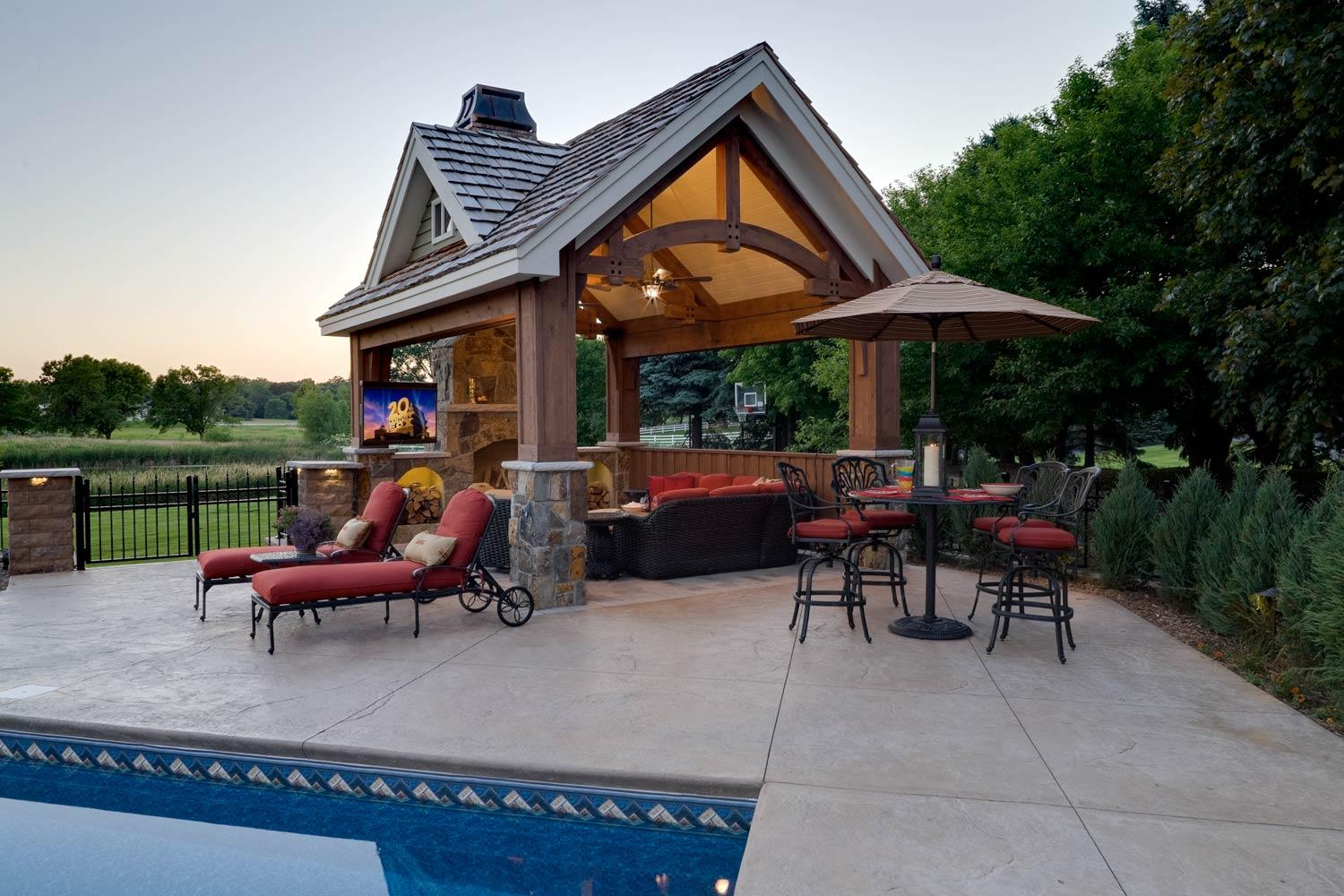 timber frame pool house structure and outdoor living room by a swimming pool