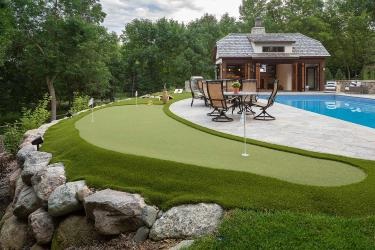 Poolside putting green and outdoor game space.