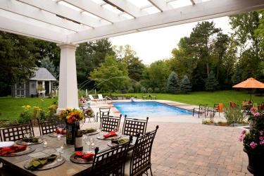 Gala backyard with outdoor dining room. White pergola shelter. Brick paver patio.