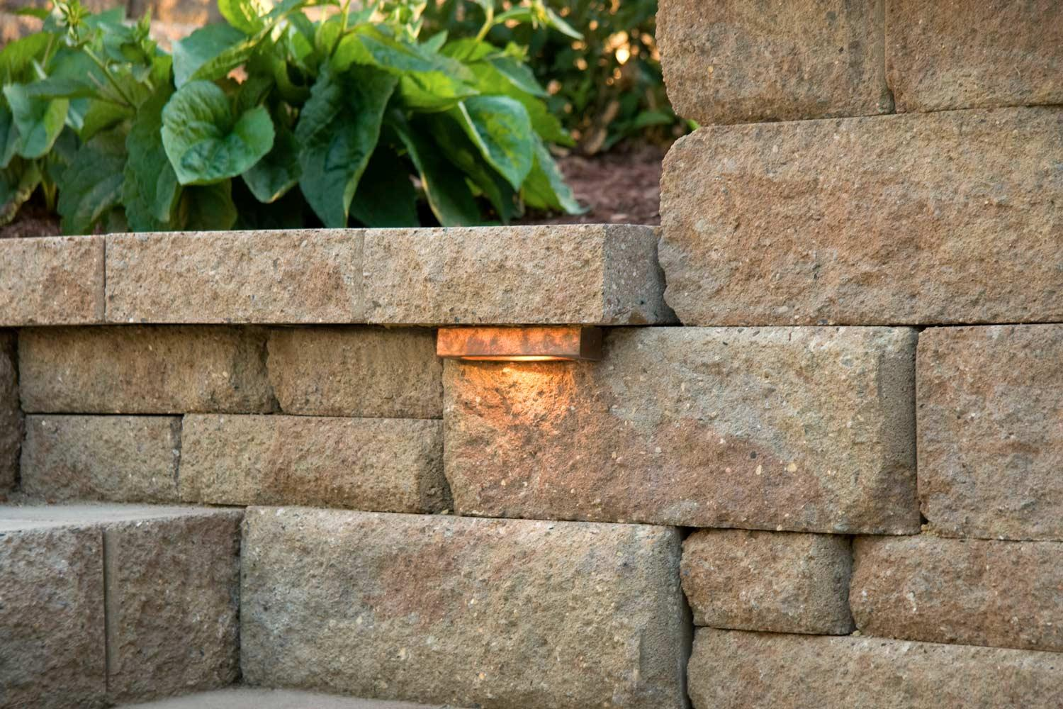 Textured modular stone block retaining wall with built-in copper wall sconces..