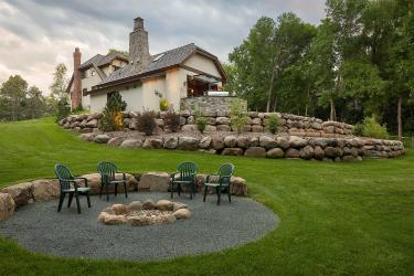 Glacial boulder retaining wall with shrubs and trees. In the foreground, a rustic campfire circle.