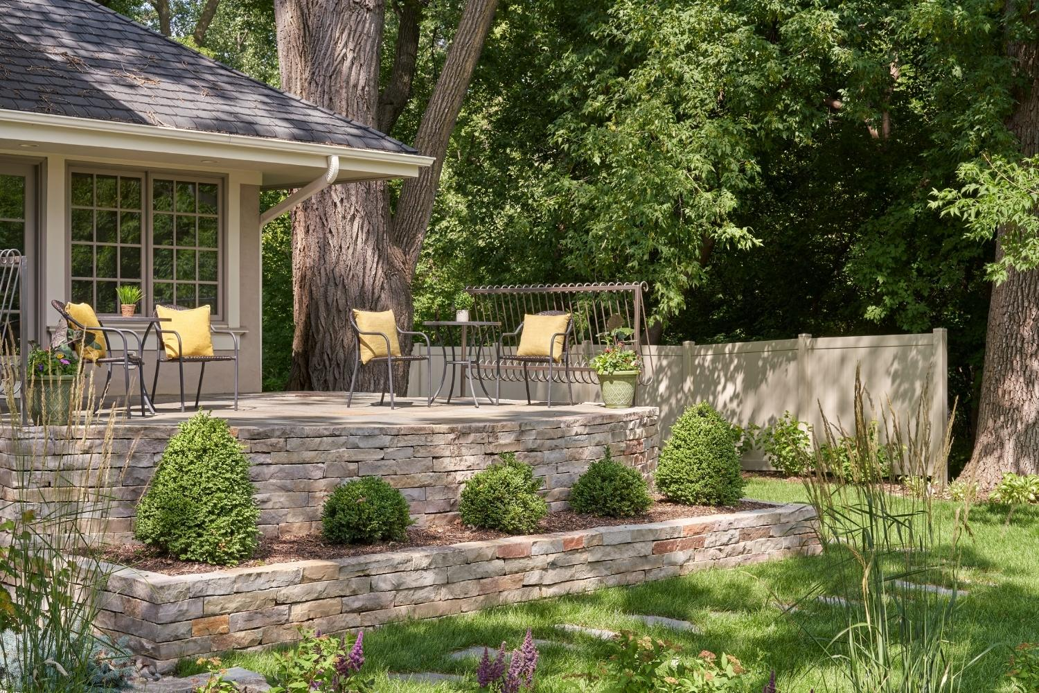 Cafe patio with wicker chairs, low retaining walls, shrubs, steppers