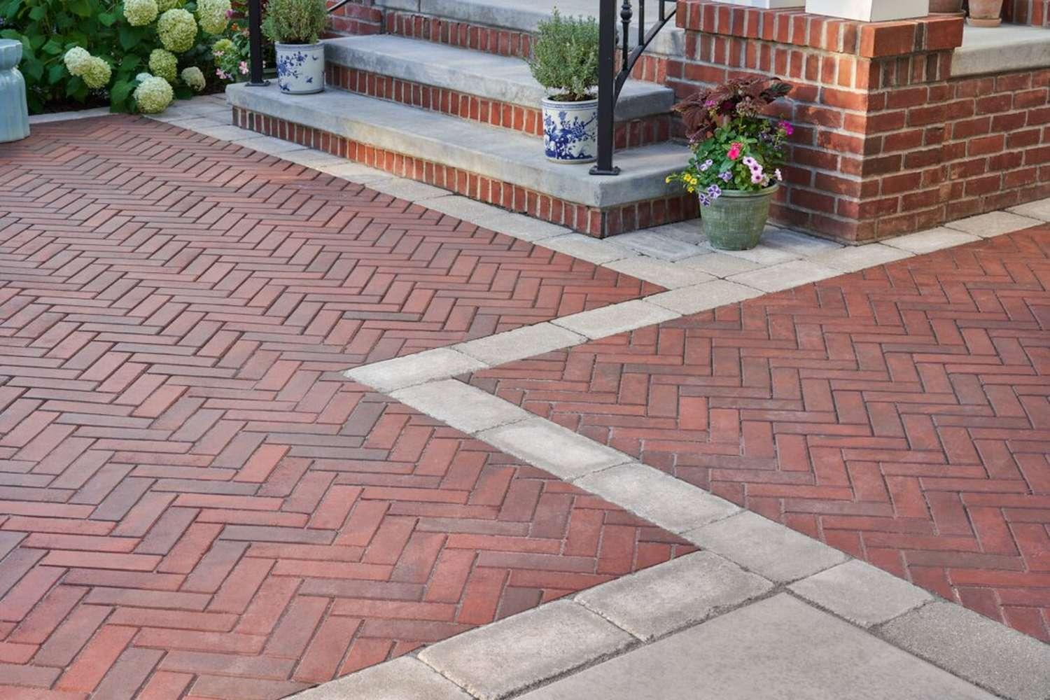 brick front steps with clay paver patio in herringbone pattern concrete paver border