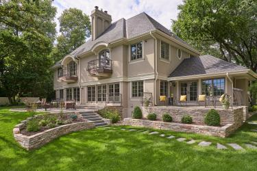 Traditional/formal style home with two patios, retaining walls and steppers leading to the front of the home.