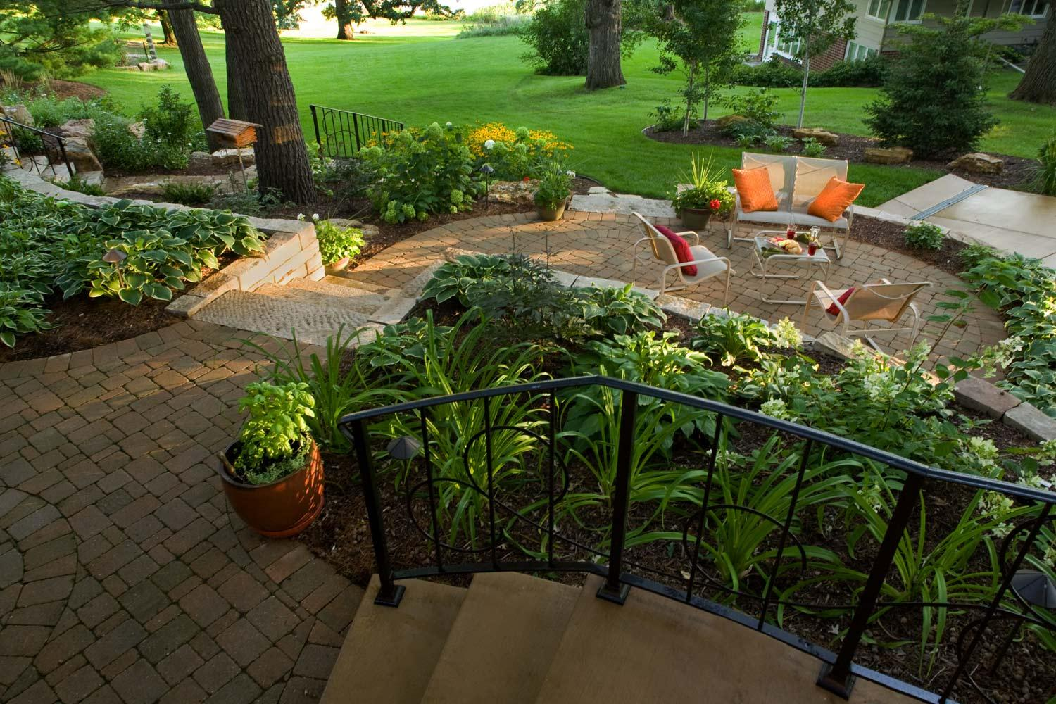 multi-level patios with brick pavers and custom railing