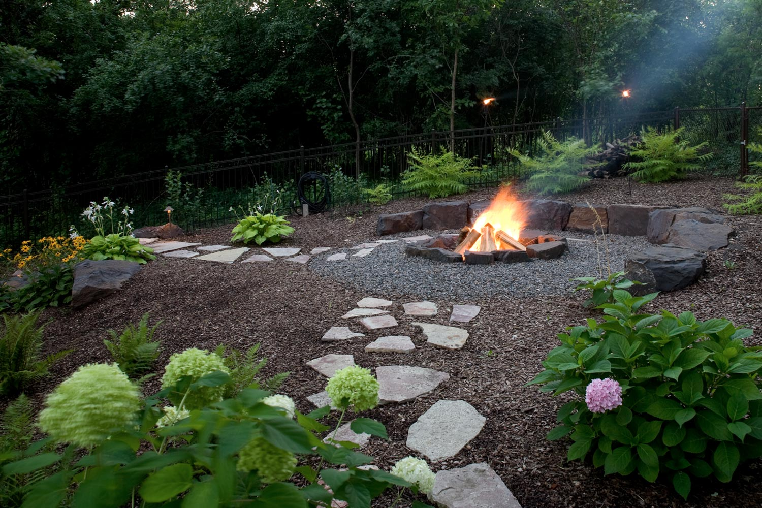 Flagstone paver walkways leading to an in-ground fire pit surrounded by crushed gravel.